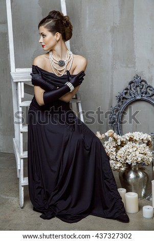 Beautiful young fashion caucasian model in black long dress and fashion makeup and beautiful hairdo posing sitting on the chair and looking at camera. Studio shot.