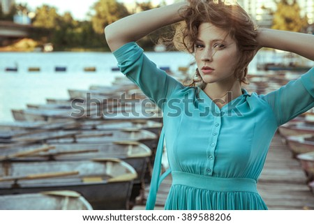 Beautiful young fashion model in green turquois dress and fashion makeup and hairstyle is posing on pier, posing and looking at camera. close up.