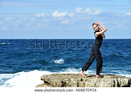 beautiful young fashion model posing on rocks near to sea
