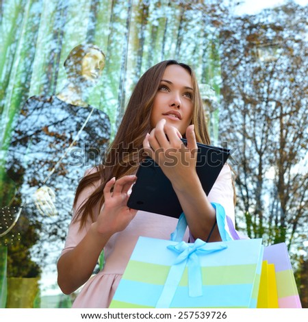 Beautiful young fashion woman holding shopping bags and standing near shop with tablet window - stock photo