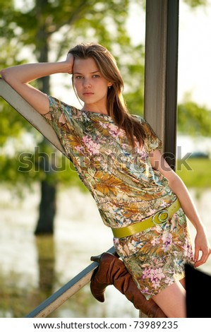 Beautiful young fashion woman in color dress posing outdoor in garden - stock photo
