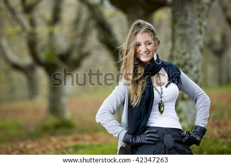 beautiful young fashion woman posing in an autumn forest