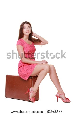 Beautiful young fashion woman posing with a old suitcase