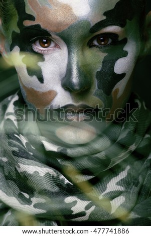 Beautiful young fashion woman with military style clothing and face paint make-up, khaki colors, halloween celebration close up, green pattern