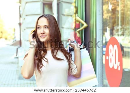 Beautiful young fashion woman with shopping bags near shop window calling smart phone, toned - stock photo