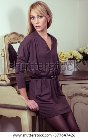 Beautiful young fashion 30-35 years blonde model in brown dress and black shoes and makeup and hairstyle and fair hair posing near the secretaire and looking at camera in provence design interior. - stock photo