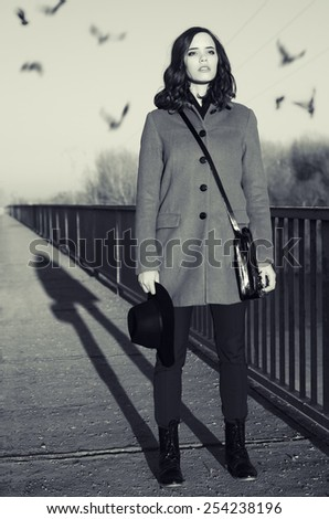 Beautiful young fashionable lady standing on bridge at sunrise while birds are flying over her head. - stock photo