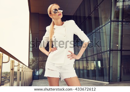 Beautiful young fashionable woman in stylish white suit jacket , shorts ripped jeans, posing in the city. Fashion photo - stock photo