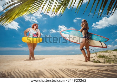 Beautiful young fat woman and skinny girl on the summer beach - stock photo