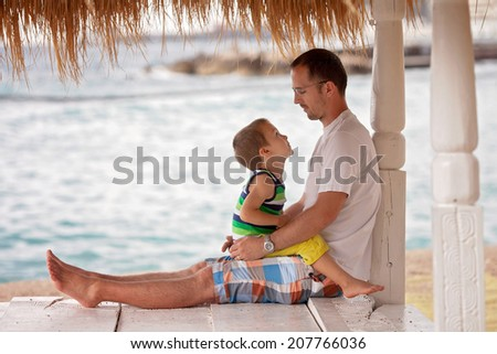 Beautiful young father, embracing his child on the beach on a cloudy day  - stock photo