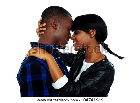 Beautiful young female about to kiss her boyfriend against white background - stock photo
