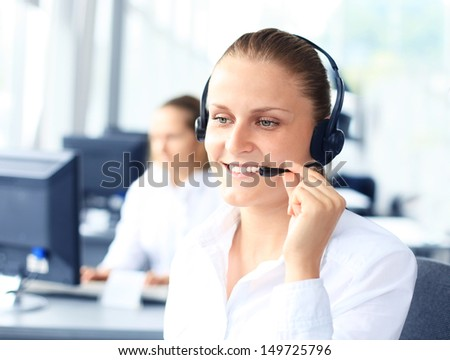 Beautiful young female call center operator with headset in office  - stock photo
