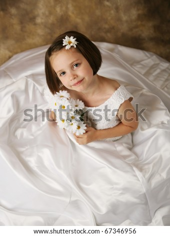 Beautiful young female child wearing her mother's wedding dress which is too big for her - stock photo