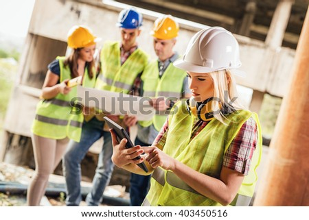 Beautiful young female construction architects using digital tablet at a construction site. Her colleagues review plan in background. - stock photo