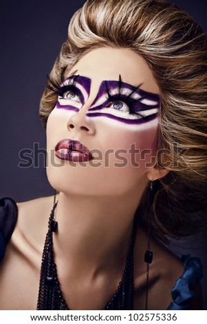 Beautiful young female face with bright fashion multicolored make-up