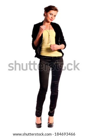 Beautiful young female fashion Model dressed in black fitting trousers, black jacket and yellow top on high heels standing