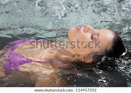 Beautiful young female floating on her back in a Jacuzzi at health spa - stock photo