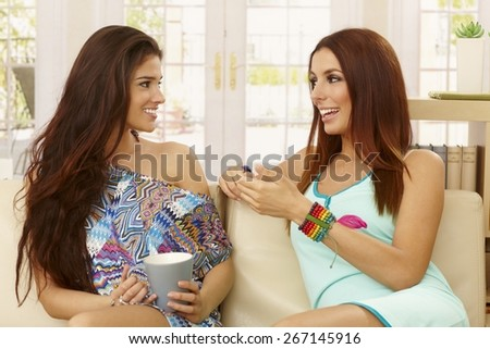 Beautiful young female friends sitting at home on sofa, talking, smiling.