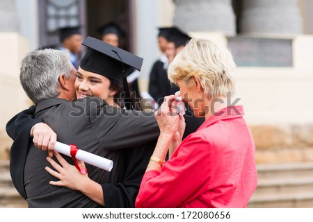 beautiful young female graduate hugging her father at graduation - stock photo