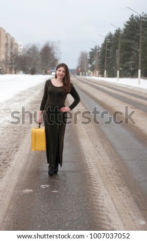Beautiful young female hitchhiking at the road