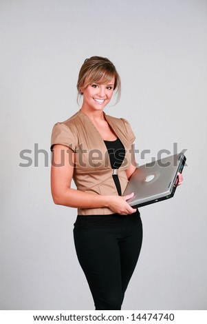 beautiful young female in business clothes holding a laptop computer - stock photo