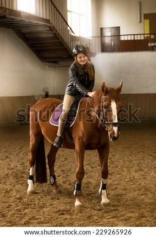 Beautiful young female jockey siting on brown horse in riding hall - stock photo