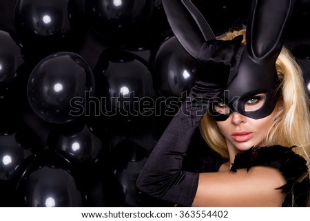 beautiful young female model in a black carnival mask, rabbit ears standing against the black balloons and sensually looks at the camera, wearing long gloves with mesh and amazing makeup - stock photo