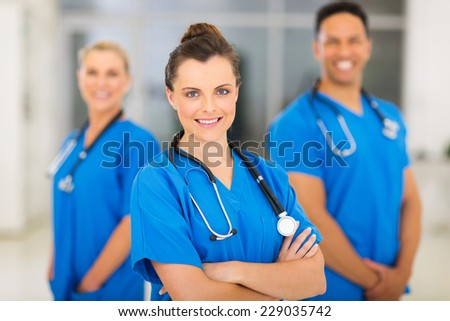 beautiful young female nurse with colleagues on background - stock photo