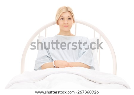 Beautiful young female patient lying in a hospital bed and posing isolated on white background - stock photo