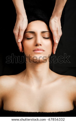 beautiful young female receiving gentle facial massage, eyes closed - stock photo