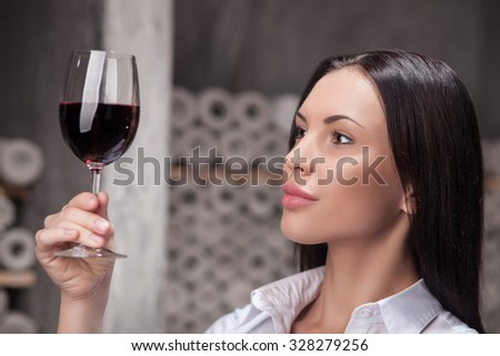Beautiful young female sommelier is analyzing sort of red wine. She is looking at wineglass with aspiration. The woman is standing in cellar - stock photo