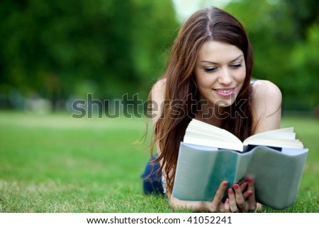 beautiful young female student reading a book outdoors - stock photo