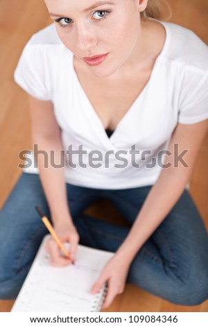 Beautiful young female student taking notes while studying and smiling into the camera