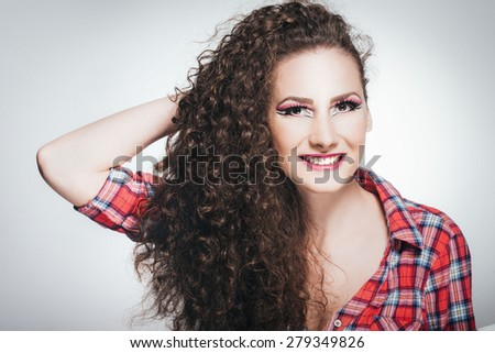 Beautiful young female with curly hair standing on white background. She is smiling. Developed from RAW, Small amount of grain added for best final impression/Beautiful young female - stock photo
