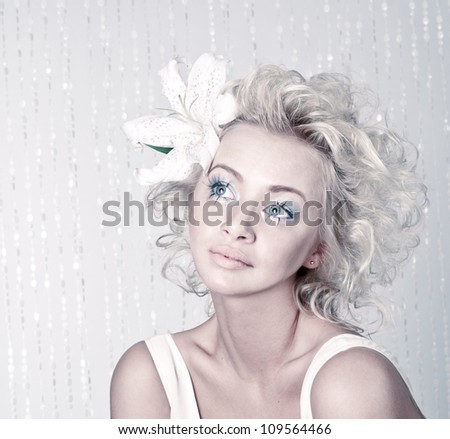 Beautiful young female with original make up, hairdress and flower