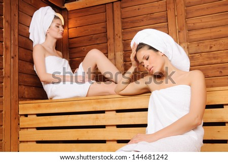 Beautiful young females relaxing in wooden spa room, eyes closed - stock photo