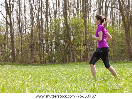 Beautiful young fit girl running outdoors - stock photo