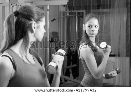 Beautiful young fitness girl exercising with dumbbells in home made gym. - stock photo
