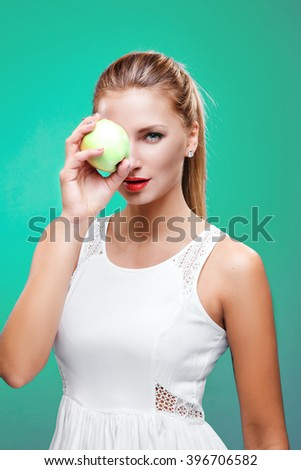 Beautiful young fitness woman happy smile hold green apple. Healthy lifestyle photo isolated on blue background. - stock photo