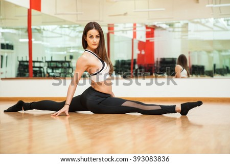 Beautiful young flexible woman doing a leg split at the gym and making eye contact