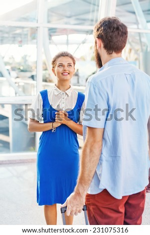 Beautiful young flight attendant in the airport explaining the way - stock photo