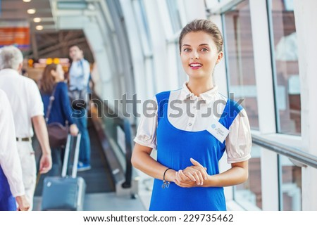 Beautiful young flight attendant in the airport. Unfocused passengers on a background - stock photo