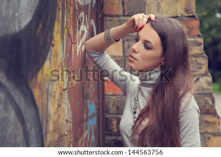 beautiful young girl against brick wall - stock photo