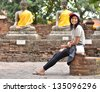 Beautiful young girl and buddha at Wat Yai Chai Mongkol Temple. Ayutthaya - Thailand - stock photo