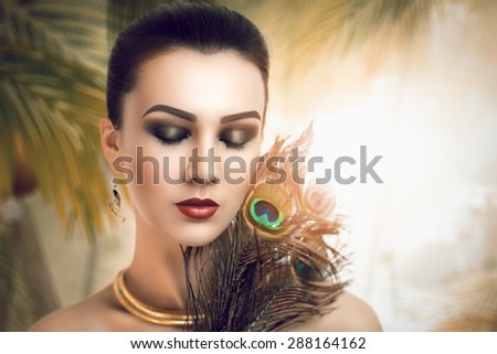 Beautiful young girl. Attractive, mysterious, interesting lady. Beauty east. Perfect holiday, expressive creative makeup, peacock feathers. Bright harmonious colors, green yellow golden. New art idea - stock photo