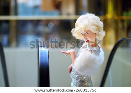 beautiful young girl, blonde, in the image of Monroe, in a silver dress, posing coquettishly - stock photo