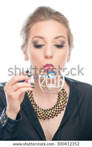 Beautiful young girl blowing soap bubble with New Year numbers 2016 - stock photo