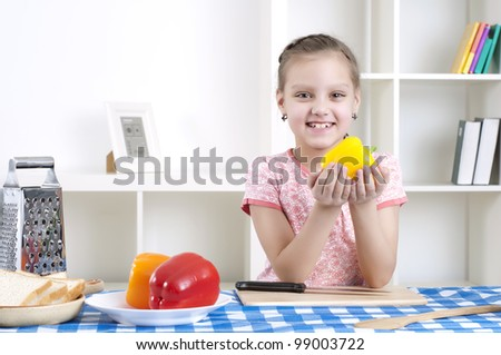 beautiful young girl cooking vegetables for a salad, working in kitchen