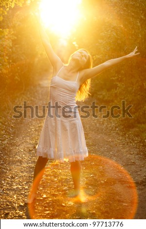 Beautiful young girl dancing in the golden light of the setting sun on forest track