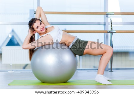 Beautiful young girl doing exercises with fit ball at gym. - stock photo